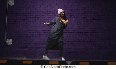 A stylish hipster girl in fashionable glasses and a hat dances near a brick violet wall in the headphones. Slow Mo