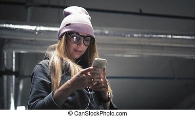 A stylish hipster girl in fashionable glasses using app on...