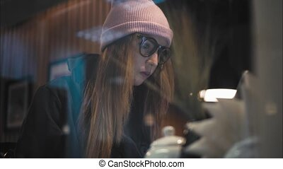 A stylish hipster woman sitting in cafe and working with laptop. View through the window