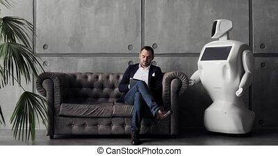 A stylish man communicates with a robot, presses a plastic...