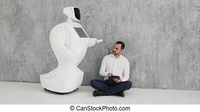 A stylish man communicates with a robot, presses a plastic...