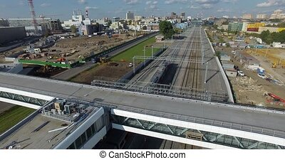 Aerial view of a suburban area with a flat bridge over railways and a moving train