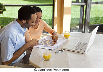 A successful African American man and woman couple in their thirties using a laptop computer to look for property on the internet