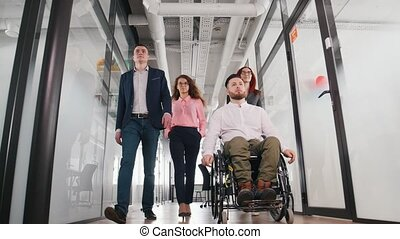 A successful business people walking through the bright corridor. A man in a wheelchair going first