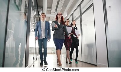 A successful business people walking through the corridor holding papers