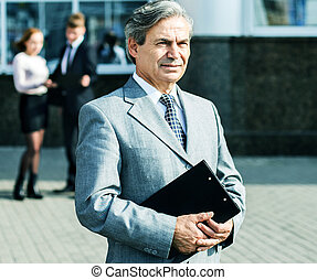 a successful businessman with documents on the background of the office