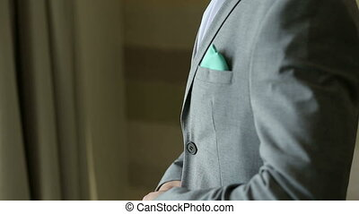 A successful young man fastens buttons on his jacket standing near the window.