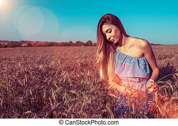 A summer dress girl walks over a wheat floor and collects wheat ears. In the summer in fresh air.