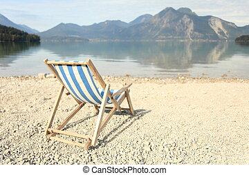 a sunchair is standing on the beach