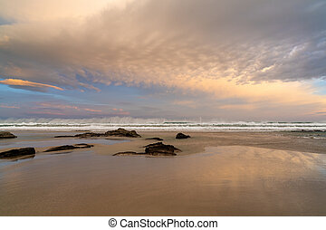 sunrise on a beautiful empty beach with waves crashing and rocks in the sand