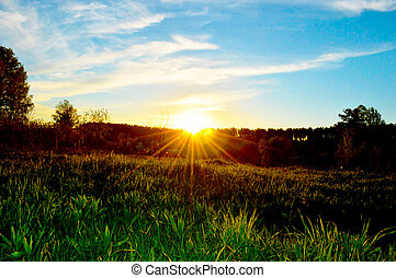 a sunset over a grass field