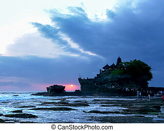 a sunset shot of pura tanah lot temple on the island of bali
