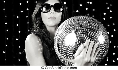a super sexy woman dances holding a discoball