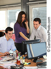 a supervisor at phone and colleagues in an office