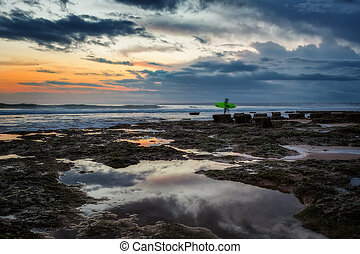A surfer coming out of raging sea to the shore. A beautiful sunset in the evening.