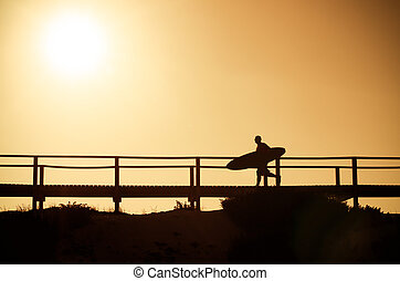 A surfer running to the beach