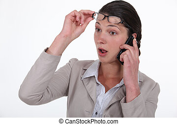 A surprised businesswoman over the phone.