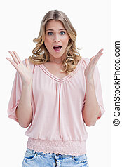 A surprised woman has her arms held up in front of her