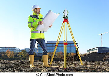 Surveyor on a hill holding a Plan roll in hands