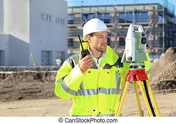 Surveyor with surveying instrument and radio in front of a new buillding