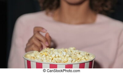 A sweet girl chews popcorn while watching a movie. Cinema, entertainment and people concept - happy friends watching movie in theater. Couple and other people eating popcorn and drinking soda while watching movie at the cinema.