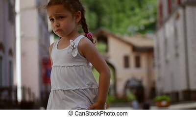 A sweet little curly girl with golden hair is sad and at the same time spinning in the dance and rotating in the street against the backdrop of the mountains. Average deceleration.