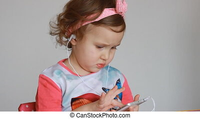 A sweet little girl thumbs a playlist on the smartphone, picks and listens to the song in the headphones. Funny child with a mobile phone in his hands chooses an application for listening to music