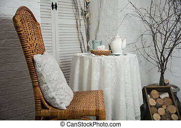 A table covered with thick cloth with a cup of tea and tea and marshmallow in a wicker plate. Tea Party