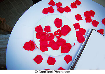 A table designed for engagement. Table setting in honor of Valentine's Day close-up . Rings and red petals inside the white plate.