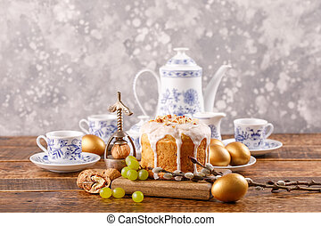 A table prepared for Easter. Easter tea drinking. Delicious home Russian cake with raisins and nuts and eggs painted in gold. Vintage service and antique nutcracker.
