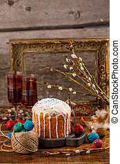 A table served for Easter. Fresh Russian cake and dyed quail eggs on a wooden background. With an ancient frame in the background. Easter greeting card.