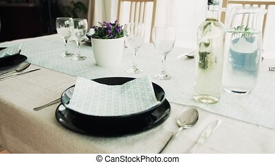 A table set for dinner at home. Plates, glasses, jug with...