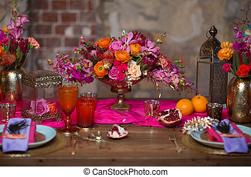 A table set vase with flowers, plates decorate in purple and pink