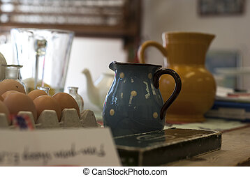 A table top of colourful clutter of jugs, teapots, bit and bobs