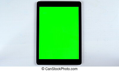 A tablet with a green screen lies on the table. Chroma Key on Gadget Screen.