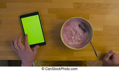 A tablet with green screen on the kitchen table