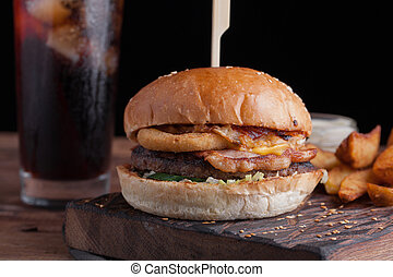A tasty Burger with snacks in the form of potatoes with white garlic sauce and a glass of cold Cola. juicy Burger with onion rings, bacon and cheese on a dark wood background.