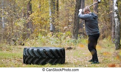 A tattooed man bodybuilder hitting the truck tire with a metal hammer - autumn forest. Mid shot