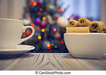A tea cup and a bowl of cookies on a wooden table against decorated Christmas tree