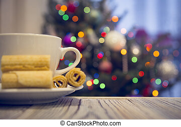 A tea cup with cookies on a wooden table against decorated Christmas tree