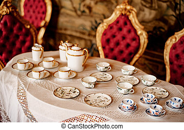 A tea set with a blue pattern and a golden set on a tray on a white mantel with molding against the background of a red wall with patterns.