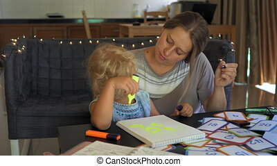 A teacher, a tutor for home schooling. a teacher or mom at the table with a little girl. Homeschooling concept.