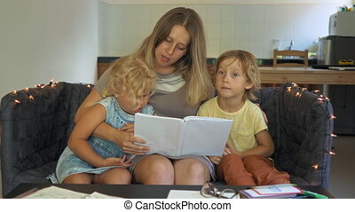 A teacher, a tutor for homeschooling. a teacher or mom at the table with little girl and boy. Homeschooling concept.