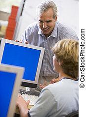 A teacher talks to a schoolboy using a computer in a high school