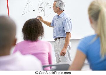 A teacher talks to school children in a high school class