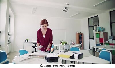A teacher walking around desks in class, preparing for ...