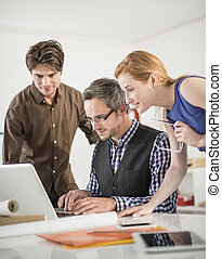 team discusses about a work project around a computer