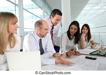 A team of architects discussing a drawing