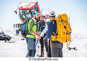 A team of climbers led by a guide discusses the upcoming ascent