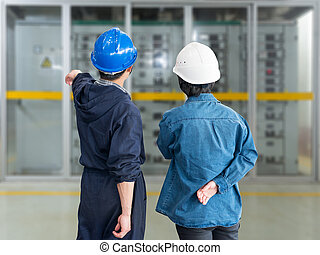 A team of construction workers with helmets at work place in a f
